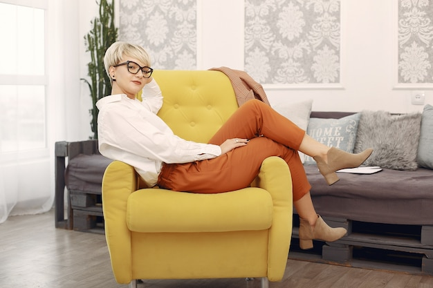 Psychologist with glasses sitting on a chair at the office Free Photo