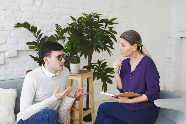Psychology, therapy, psychiatry, mental health and counseling concept. candid shot of nervous self conscious young male in glasses telling middle aged female counselor about his problems at work Free Photo