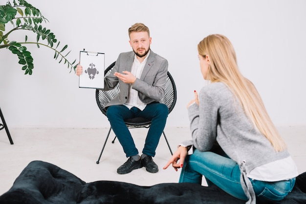 Psychotherapist showing rorschach test card to female patient in clinic Free Photo