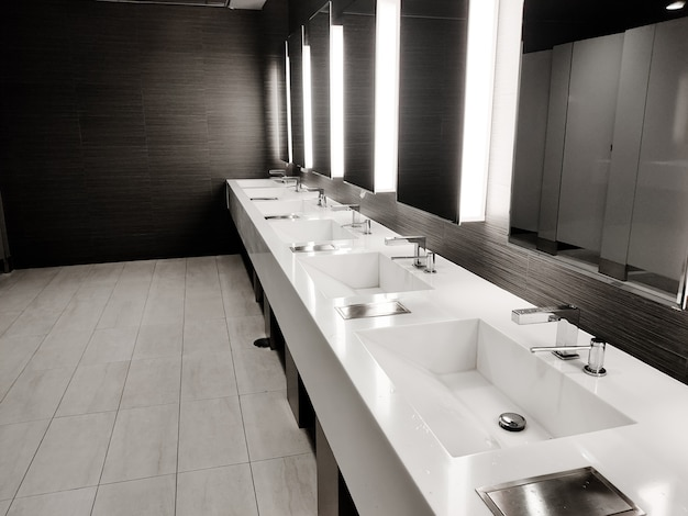 Public empty restroom with washstands, baby changer, and toillets in mirror. white sink row with mirrors and lights. top horizontal view copyspace Premium Photo