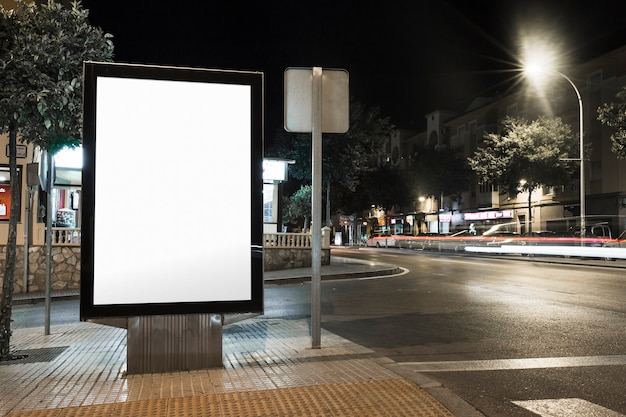 Public information board with blurred vehicles lights in city Free Photo