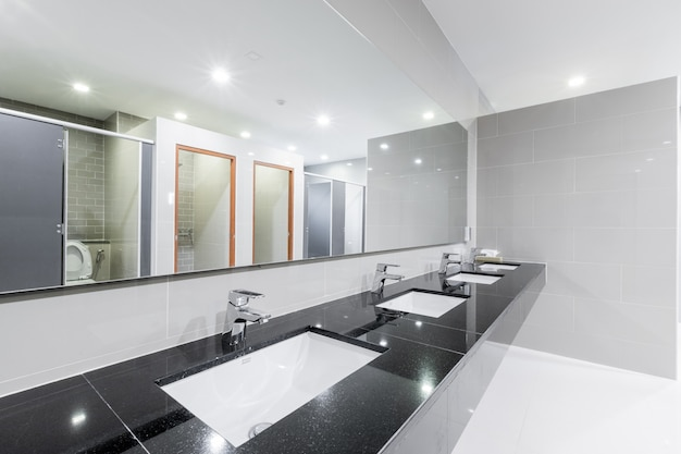 Public interior of bathroom with sink basin faucet lined Premium Photo