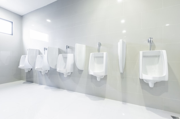 Public toilet urinals lined up Premium Photo
