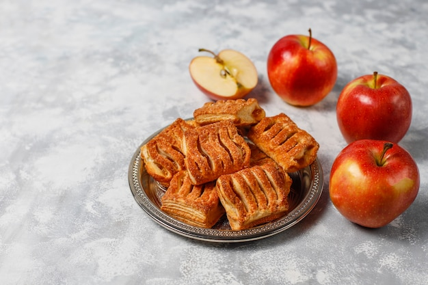 Puff pastry cookies filled with apple jam and fresh red apples on light concrete Free Photo