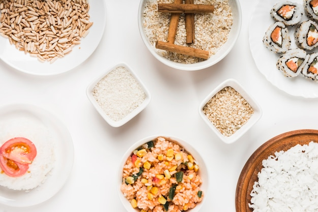 Puffed rice; chinese fried rice; uncooked rice with cinnamon sticks and sushi on white background Free Photo