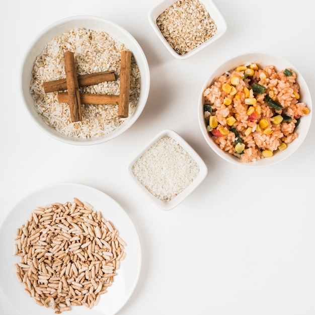 Puffed rice; chinese fried rice and uncooked rice with cinnamon sticks on white backdrop Free Photo