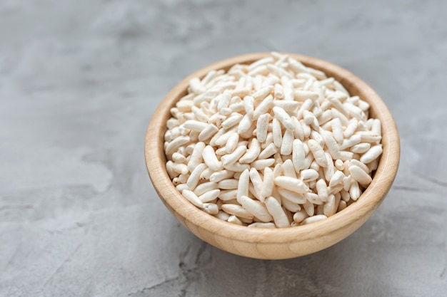 Puffed rice in a wooden bowl on a gray background Premium Photo