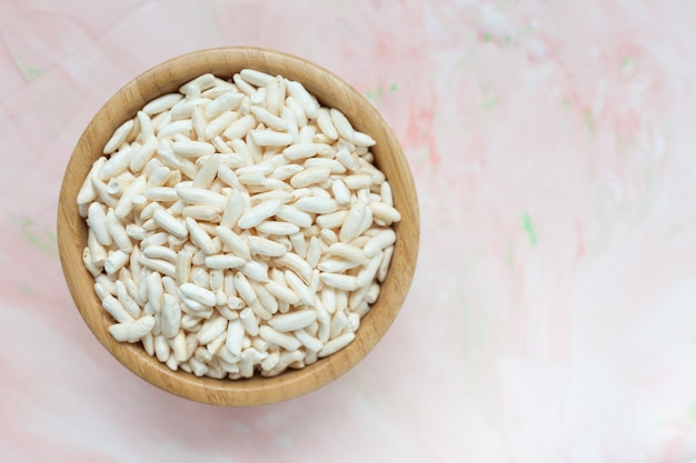 Puffed rice in a wooden bowl on pink Premium Photo