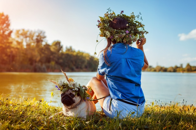 Pug dog and its master chilling by river wearing flower wreaths. happy puppy and woman enjoying summer nature outdoors Premium Photo