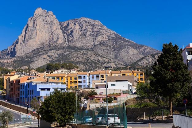 Puig campanaの崖のふもとにあるカラフルな家のあるスペインの村fenestrat。 Premium写真