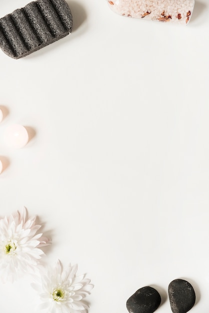 Pumice stone; salt; la stone; candles and flower on white background Free Photo