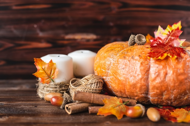 Pumpkin, acorns, yellow leaves, cinnamon on a dark background Premium Photo