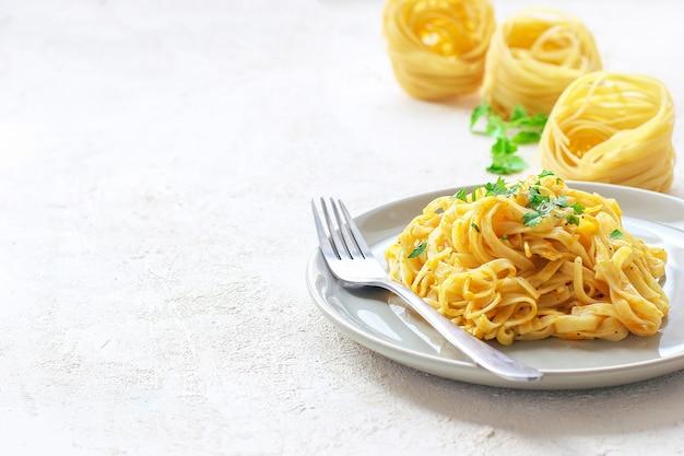 Pumpkin alfredo fettucine pasta in a ceramic plate with fresh raw butternut squash slices. autumn meal for lunch. butternut squash recipe. Free Photo