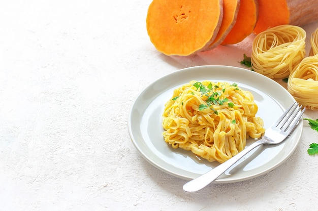 Pumpkin alfredo fettucine pasta in a ceramic plate with fresh raw butternut squash slices. autumn meal for lunch. butternut squash recipe. Free Photo