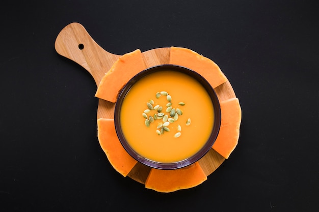 Pumpkin and soup on black background Free Photo