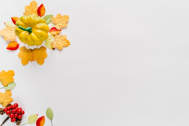 Pumpkin and autumn leaves in arrangement Free Photo