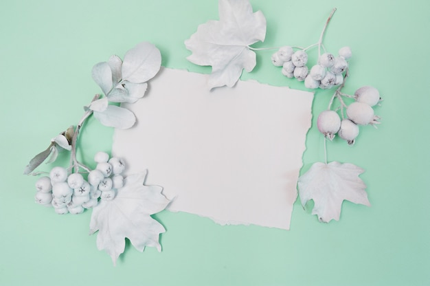 Pumpkin, berries and leaves with white frame on a green pastel surface Premium Photo
