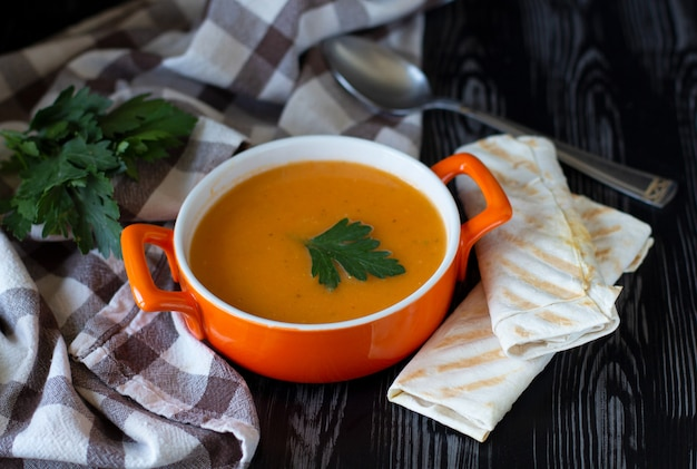 Pumpkin carrot cream soup in an orange plate with cheese pita on a checkered tablecloth with wooden background Premium Photo