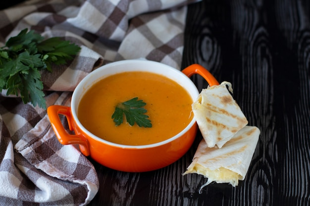 Pumpkin carrot cream soup in an orange plate with cheese pita on a checkered tablecloth Premium Photo