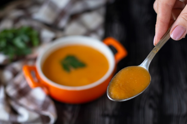 Pumpkin carrot cream soup spoon in an orange plate with cheese pita on a checkered tablecloth Premium Photo