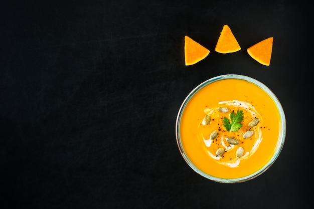 Pumpkin and carrot soup with cream, pumpkin seeds and parsley on dark scratched background. Premium Photo