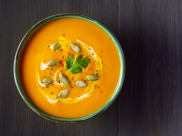 Pumpkin cream soup in a bowl with pumpkin seeds, parsley and cream on wooden table. Premium Photo
