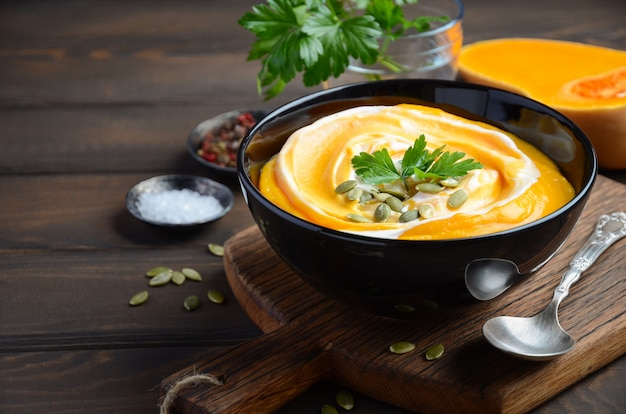 Pumpkin cream soup with cream and pumpkin seeds on wooden table. Premium Photo