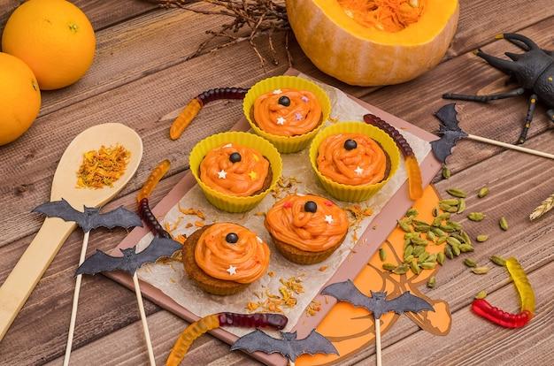 ハロウィーンのオレンジクリームとカボチャのカップケーキ。お菓子作り、焼き菓子のアイデア。 Premium写真