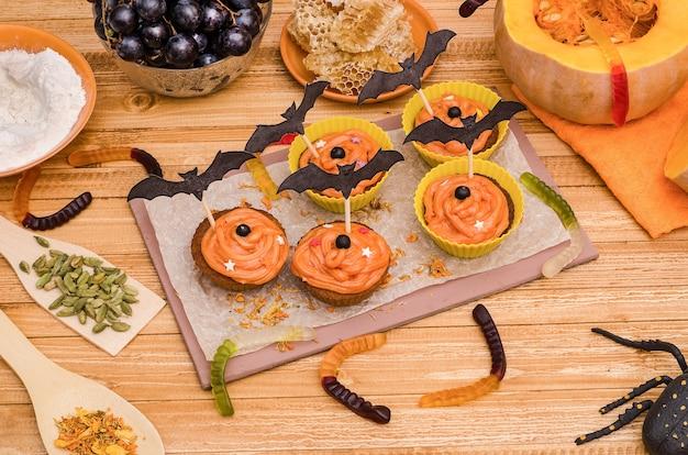 Пирожные из тыквы с апельсиновым кремом на хэллоуин. идеи для выпечки, сладостей. Premium Фотографии