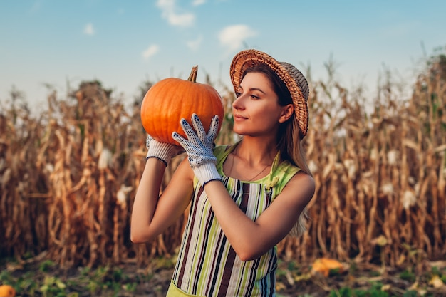 Pumpkin harvest. young woman farmer picking autumn crop of pumpkins on farm. agriculture. thanksgiving and halloween Premium Photo