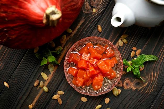 Варенье из тыквы на темной деревянной поверхности с тыквой, мятой и тыквенными семечками Premium Фотографии