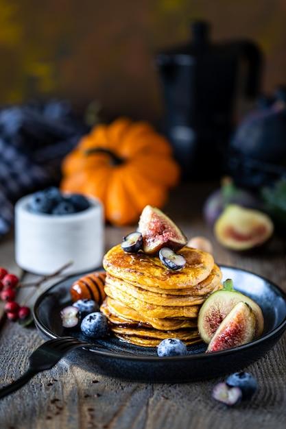 Тыквенные оладьи с сиропом или медом, семенами льна, инжиром, черникой в темной тарелке на столе, выборочный фокус, копия пространства Premium Фотографии