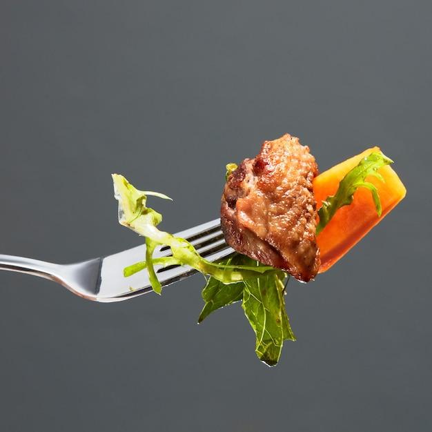 호박, 오리 고기 조각, 포크에 샐러드 프리미엄 사진