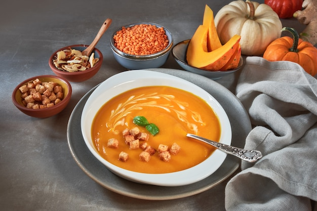 Pumpkin and red lentil creme soup in ceramic bowl seasoned with basil, cream and croutons Premium Photo