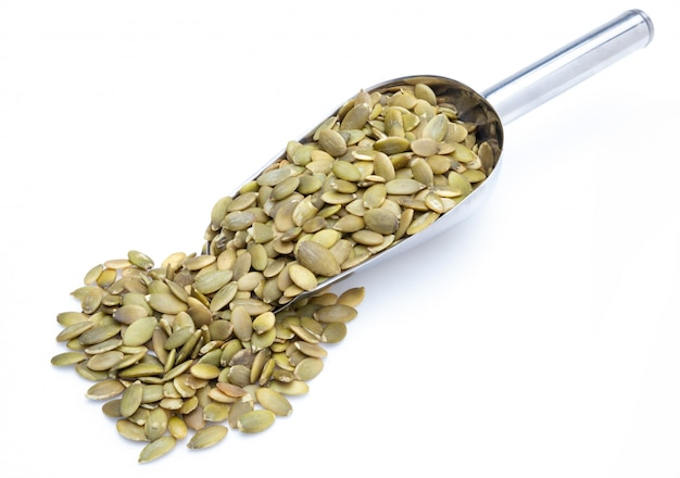 Pumpkin seeds (peeled seeds) in metal shovel (collection of various nuts). isolated Premium Photo