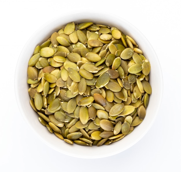 Pumpkin seeds (peeled seeds) in white bowl (various nuts collection). isolated Premium Photo