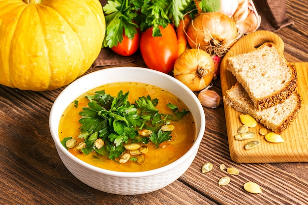 Pumpkin soup and fresh vegetables on wood Premium Photo