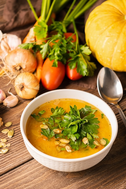 Pumpkin soup and fresh vegetables on a wooden table Premium Photo