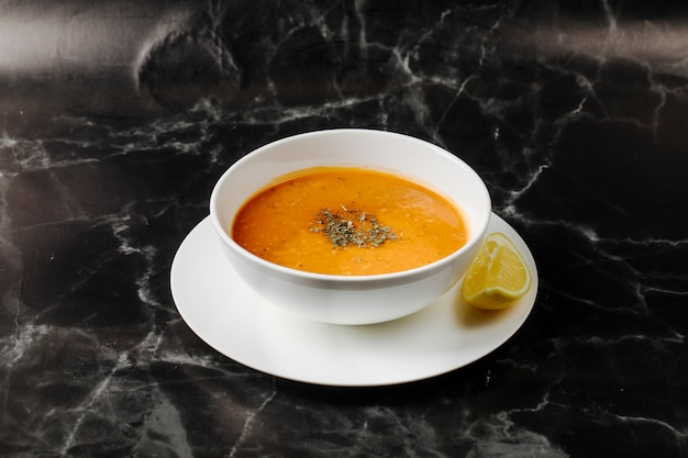 Pumpkin soup inside white bowl with herbs and spices on it with a slice of lemon around. Free Photo