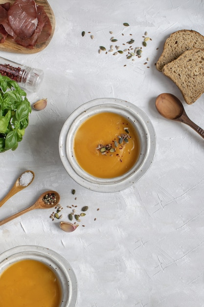 Pumpkin soup plate top view, gray background, copy space. Premium Photo