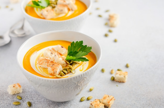 Pumpkin soup with cream, croutons, pumpkin seeds and parsley on a gray concrete or stone background. Premium Photo