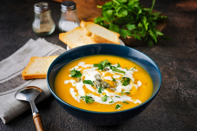 Pumpkin soup with cream and parsley on dark rustic table Premium Photo
