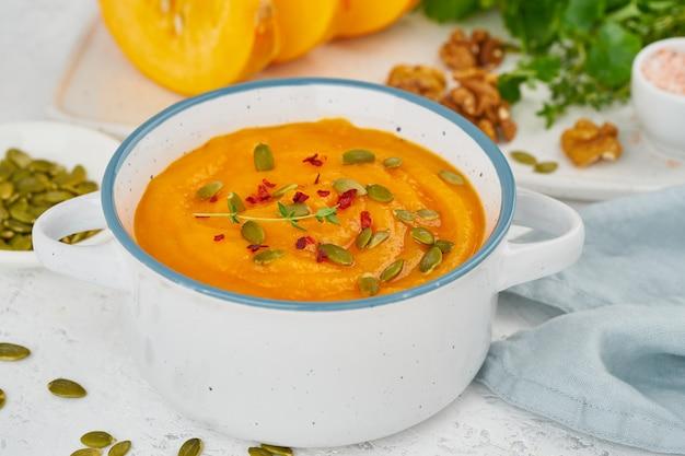 Pumpkin vegetarian cream soup with walnuts, side view on light background closeup Premium Photo