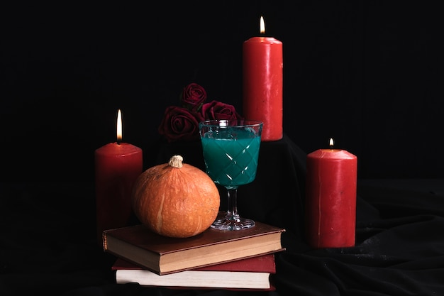 Pumpkin with green drink and candles Free Photo