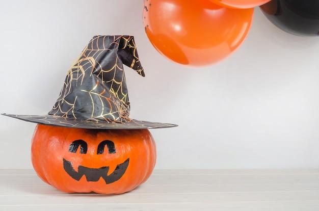 Тыква с раскрашенным лицом в шляпе ведьмы возле оранжевых и черных воздушных шаров Premium Фотографии