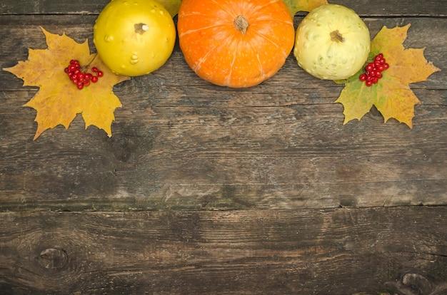 Тыквы и осенние листья на старой деревянной поверхности Premium Фотографии