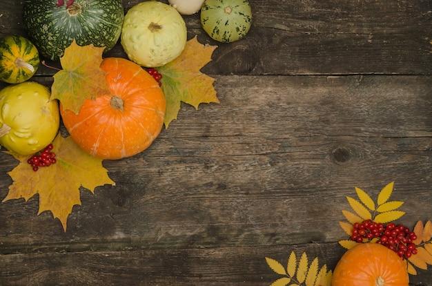 Тыквы и осенние листья на старом деревянном столе Premium Фотографии