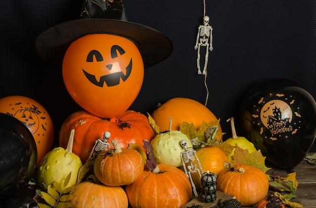 Тыквы и воздушные шары с осенними листьями и украшением на хэллоуин Premium Фотографии
