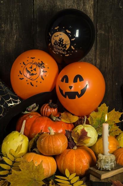 Тыквы и воздушные шары со свечой и осенними листьями Premium Фотографии