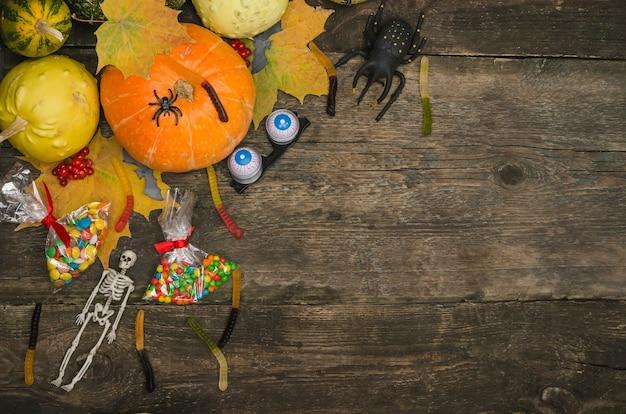 Тыквы и сладости на старом деревянном столе с пауками и скелетом Premium Фотографии